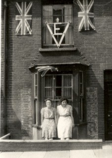 This photograph shows Rose Casey and Nora Jacob standing in front of Number 16 Rampart Road when it was decorated for the VE Day celebrations. In 1953 these flags were brought out again for the coronation of Elizabeth ll; the VE being replaced by an illuminated picture of the new Queen. | Picture by kind permission of the Jacob family