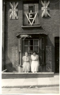 This photo was taken in 1945 when Number 16 was decorated for VE Day, my aunt and great aunt standing in front of the bay window. The drop between pavement level and the front door is just visible. | Picture by kind permission of the Jacob family