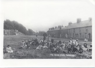 Children on the Greencroft at the start of the twentieth century. A group of about 40 children sitting on the grass of the Greencroft. The photo shows the original layout of that corner of the park, before it was changed with the building of the ring road.