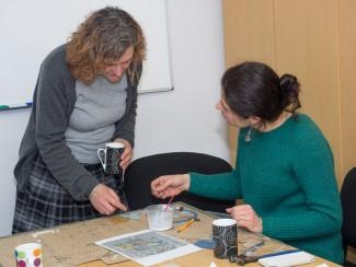 Mosaic artist Joanna Dewfall explaining how to glue on the tiles. | Photo John Palmer