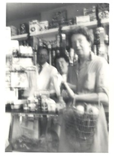 Inside the shop in the 1950s with Mr. Ralph and his shop assistant Brenda. Mr. Ralph's son David thinks the customer may have been Mrs. Izzard of Culver Street. | David Ralph