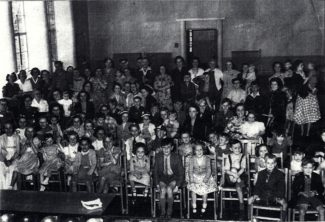 This is a picture of an event held at the school during the 1950s. At the back of the hall, the door to the foyer is open; the flower arrangement on the polished table being just visible. The closed doors on the left led into the dining room. | Taken from a photograph in Robin Safe's possession.